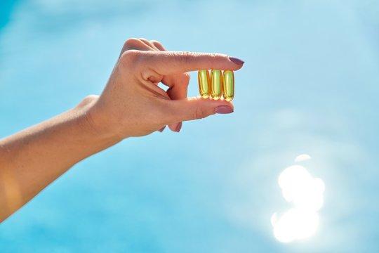 Sunny golden vitamin D oil capsules Omega-3 in woman hand