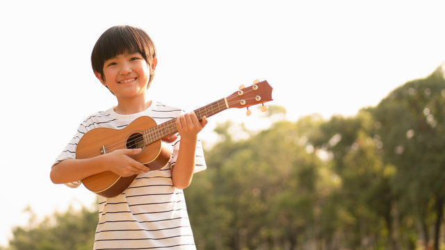 Cute Asian boy holding Ukulele with a big smile feeling happy and confident to play music in the park, carefree mind, concept musical playing, creative activity, music education, children development.