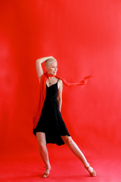Woman 40 45 years old in a black dress dancing tango on a red background.