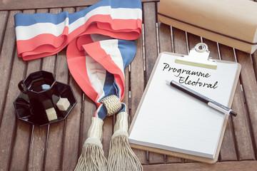 Maire et adjoints en france - élection municipale - bureau du Maire - bureau en bois avec une écharpe tricolore d'élu municipal ou de député de la République avec le programme électoral