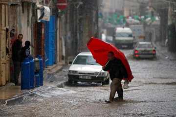 Palestinian man holds an umbrella as he walks on a street during a rainfall in Gaza