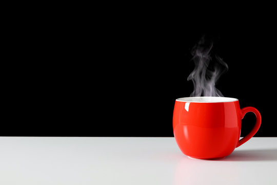Steaming coffee cup on black background. Red сoffee cup with steam. Smoke from hot coffee. Front view, copy space