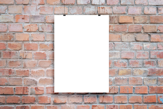Poster design presentation mockup. Blank paper poster hanging attached with clips across brick wall