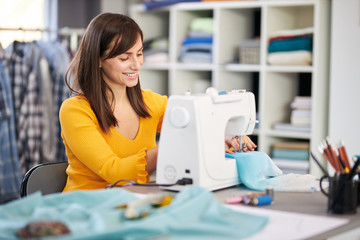 Smiling charming caucasian fashion designer sitting in her studio and sewing beautiful evening dress.