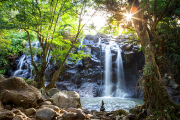 scenic view of serene waterfall in bali indonesia with sunrays flare and balancing stones