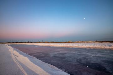 Nature reserve Saline Margherita di Savoia, Apulia, Italy: The salt pan. Salt flats area for sea salt production. A salt marsh, an ecosystem on Adriatic sea. Heaps of salt at sunset ready for harvest