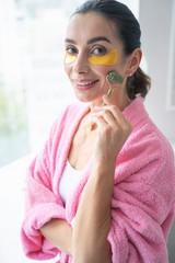 Positive woman doing facial massage at home stock photo