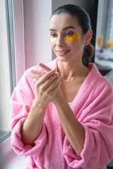 Woman in bathrobe applying hand lotion stock photo