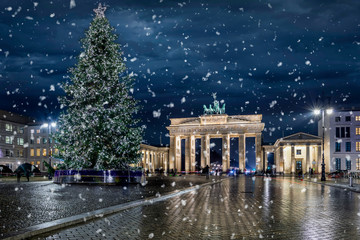 Poster Berlijn Das Brandenburger Tor in Berlin, Deutschland, mit Weihnachtsbaum bei Nacht und Schneefall
