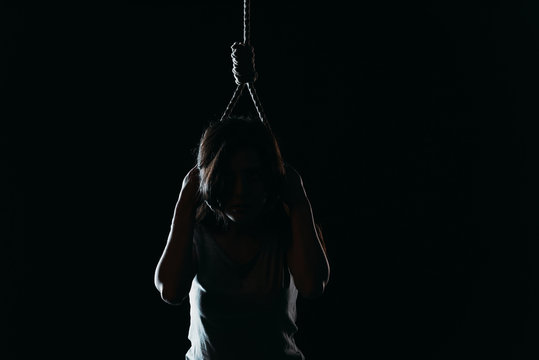 depressed woman committing suicide while putting noose on neck in darkness isolated on black