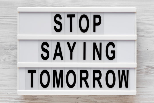 'Stop saying tomorrow' words on a lightbox on a white wooden background, top view. Overhead, from above, flat lay. Close-up.