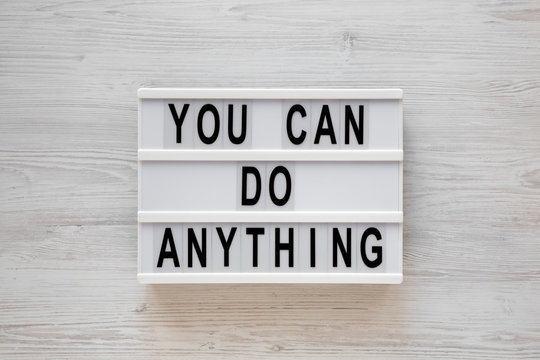 'You can do anything' words on a lightbox on a white wooden background, top view. Overhead, from above, flat lay. Closeup.