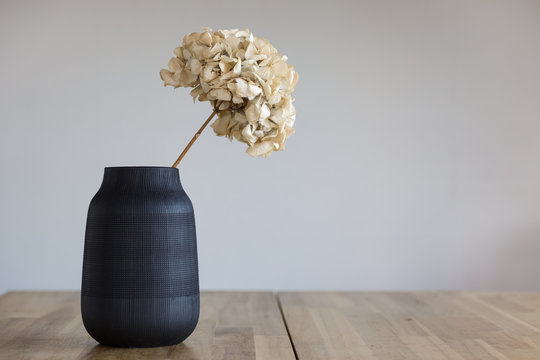 A black ceramic vase with a dried hydrangea flower stands on a wooden surface.