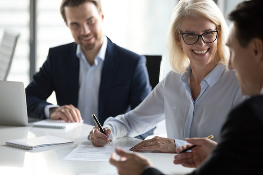 Smiling mature businesswoman signing contract, agreement at meeting