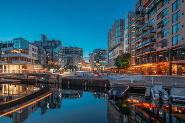Oslo, Norway. Night View Embankment And Residential Multi-storey Houses In Aker Brygge District. Summer Evening. Residential Area Reflected In Sea Waters. Famous And Popular Place