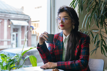 Young serious brunette business woman in glasses, dressed in plaid jacket sits at the table in the cafe and drinking coffe