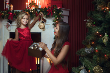 portrait of beautiful little girl with her mama in christmas environment