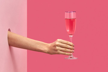 Poster Alcohol Woman's hand holds glass of rose wine with soft shadows.