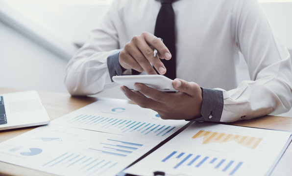 Business men use calculators to calculate the company's tax and revenue in the office, Financial and accounting banking concepts.