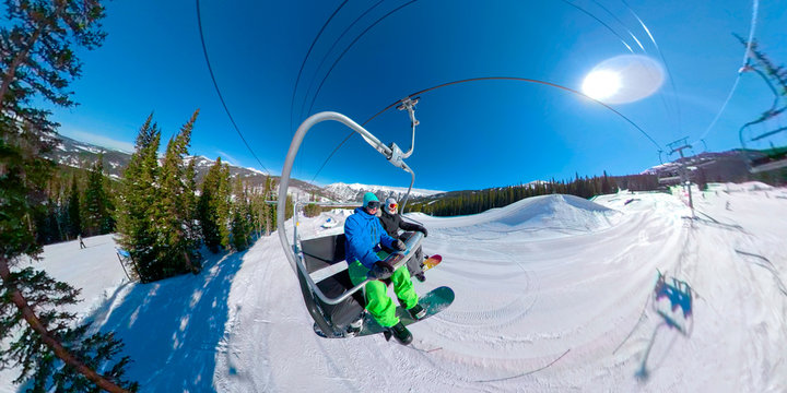 SELFIE: Happy snowboarder couple rides the chairlift on a sunny winter day.