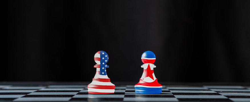 USA and North Korea flag printed screen on chess with background which both countries have conflict about nuclear weapons and sanctions crisis.