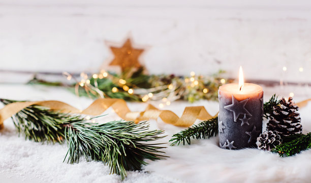 Romantic winter and christmas greeting card  - Burning candle with natural fir and pine cone decoration in scandinavian style, bright background and copy space