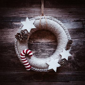 Woolen Christmas wreath, decorated with pines, white paper stars and crocheted candy canes on dark, wooden vintage background / scandinavian style