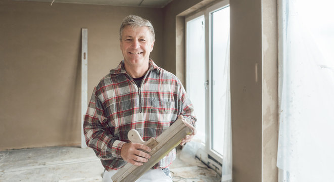 Friendly plasterer in the interior of newly constructed house
