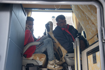 Migrants are seen in a bus near migrant camp in Vucjak
