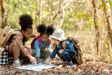 Obraz Group family children checking map for explore and find directions in the camping jungle nature and adventure. Tourism kids travel for destination and leisure trips for education and relax in nature  - fototapety do salonu