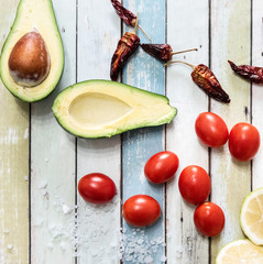 Tomatoes, avocado, chili peppers, lemon, salt on a wooden table