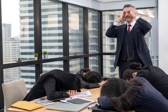 Moody or stress boss with lazy or tired teamwork sleep on meeting table in office concept