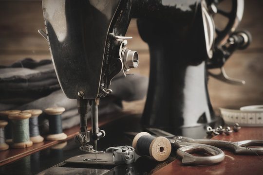 Old antique sewing machine close up. Tailoring scissors, cloths and wooden spools of threads. Retro tailor workshop.