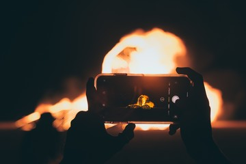 Person taking a picture of the bonfire with a smartphone at night time