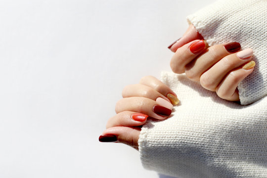 Autumn manicure in orange, brown and gold color on the white background. Warm atmosphere. Manicured woman's hands in warm white sweater.