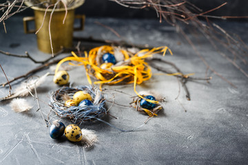 Quail easter eggs with feathers in nest on brown table with copy space.