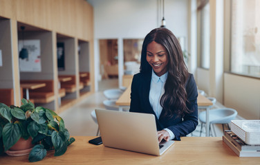 Smiling African American businesswoman using her laptop at a tab