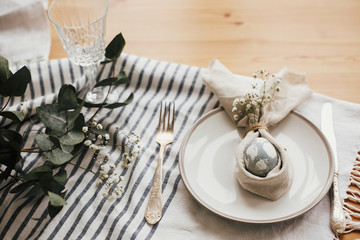 Stylish Easter brunch table setting with egg in easter bunny napkin. Modern natural dyed blue egg on napkin with bunny ears, flowers on plate and vintage cutlery. Easter table decorations