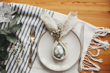 Stylish Easter brunch table setting with egg in easter bunny napkin, flat lay. Modern natural dyed blue egg on napkin with bunny ears, flowers on plate and cutlery. Easter table decoration