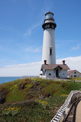Low angle view of the Pigeon Point lighthouse in northern central California located in an open public park along the famous Highway 1 seen on a bright summer day