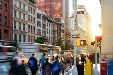 Fotomurales - Crowds of people in motion walking down the busy sidewalk on 5th Avenue in Midtown Manhattan, New York City