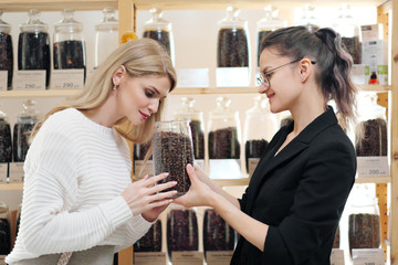 A female shopper in the store chooses a grain coffee. The seller helps the buyer.