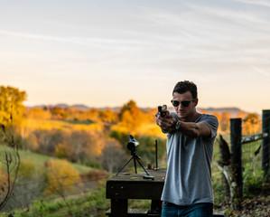 young caucasian man standing with handgun/pistol at outdoor range in Kentucky