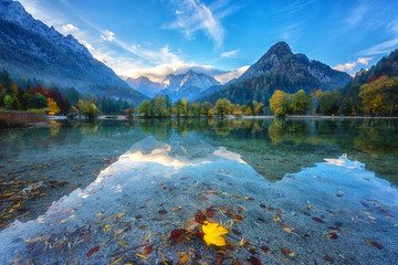Photo sur Aluminium Bleu nuit Jasna lake in Triglav national park at sunrise, Kranjska Gora, Slovenia. Amazing autumn landscape with Alps mountains, trees, blue sky with clouds and reflection in water, famous tourist attraction
