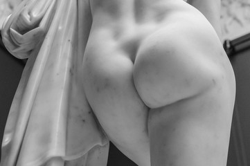 Foto op Plexiglas Ezel Antique marble woman ass sculpture. Detail of the butt of the statue of marble with solid buttocks