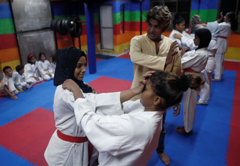 An instructor demonstrates self-defense techniques to girls at a self-defense class in Mumbai