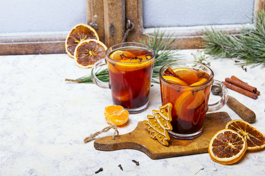 Christmas drink, mulled wine with orange, cinnamon and cloves on white background