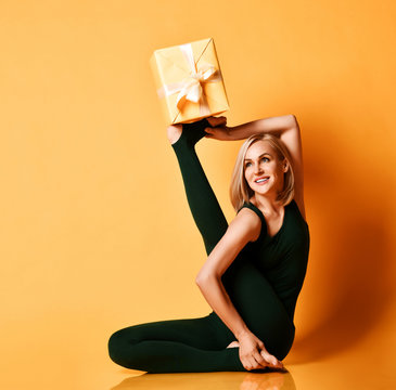 Athletic woman does yoga asana stretching exercise holds New Year Christmas gift box on her upturned leg foot on yellow