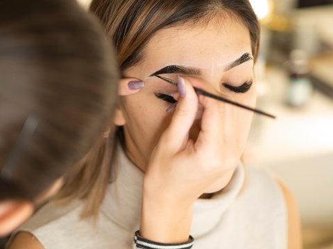 Eyebrow tinting. Close up master applying brow tint with a brush. Cosmetic procedures, eyebrow permanent makeup