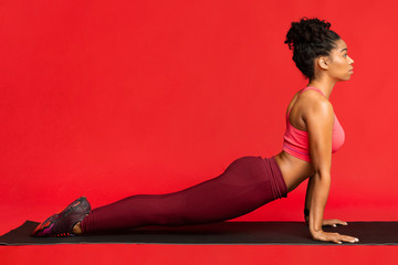 Sporty girl working out on fitness mat over red background